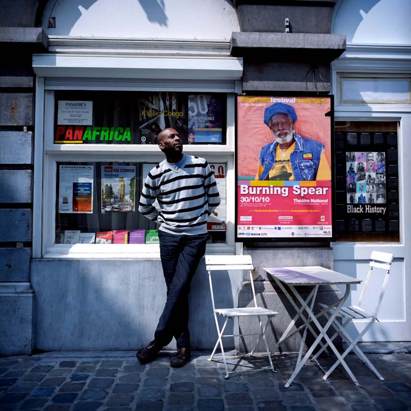 Nzema Omba, 37, in front of his bookshop <i>Panafrica</i>. Son of a Mobutu opposer imprisoned for 5 years in a Congolese prison, he studied Philosophy and Law in Belgium. In his bookshop Nzema organizes language courses, meetings, events, book presentations.  «This association is an excuse to study my land and my people. When I go back to Congo I want to be a good example for the young people in my country».